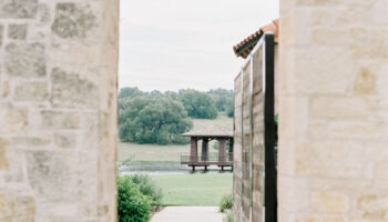 Stone archway between the main building and bridal suite of Garey House, with the lawn and dock in the distance