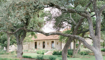 Angled view of the front entry of Garey House with arching oak trees in front