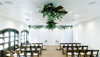 A rain plan ceremony in the Hall, with white fabric backdrop and greenery, with ceremony chairs along each side (wide shot)