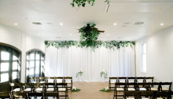 A rain plan ceremony in the Hall, with white fabric backdrop and greenery, with ceremony chairs along each side