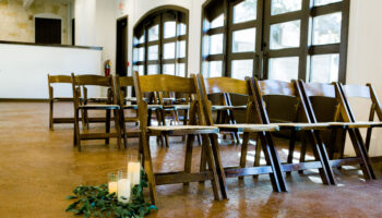 Close up of ceremony chairs for a rain plan ceremony in the Hall, with LED candles and greenery at front row, view of the french doors behind