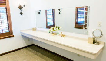 Vanity counter in the large prep suites, with long mirror and natural light coming from the open shutter windows
